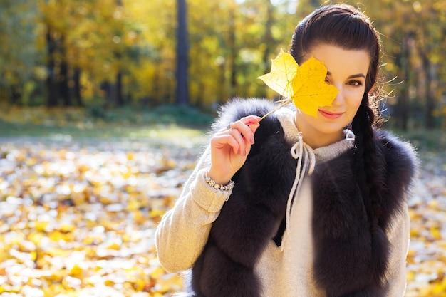 Menina fecha os olhos com uma folha de outono