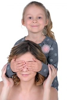 Menina fecha os olhos da mãe e sorri.