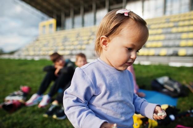 Menina fechar retrato. a família de esportes passa o tempo livre ao ar livre com patinetes e patins.