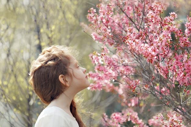 Menina fechou os olhos e respira o aroma de uma árvore florida.