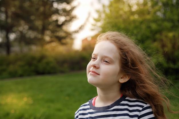 Menina fechou os olhos e respirando com ar fresco soprando.