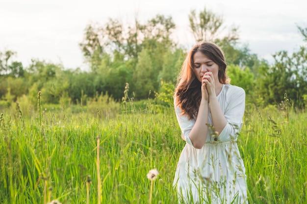 Menina fechou os olhos, orando em um campo durante o belo pôr do sol