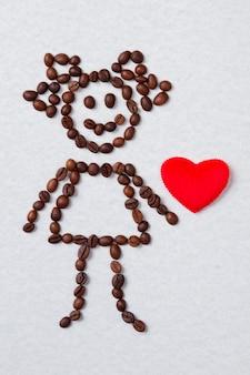 Menina feita de grãos de café e coração vermelho. conceito de amor e café. superfície isolada branca.
