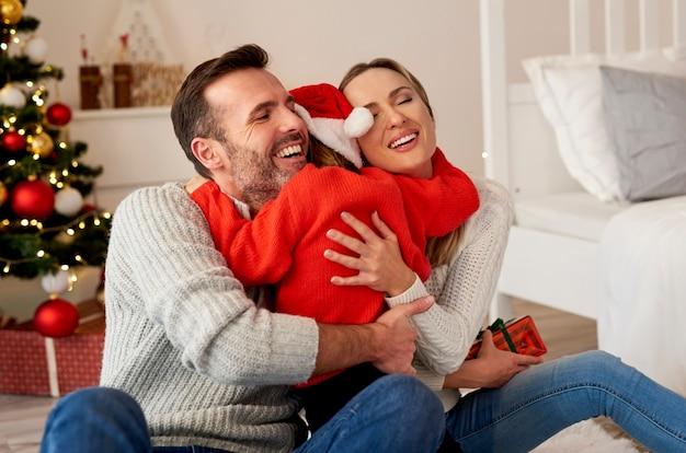 Menina feliz abraçando os pais