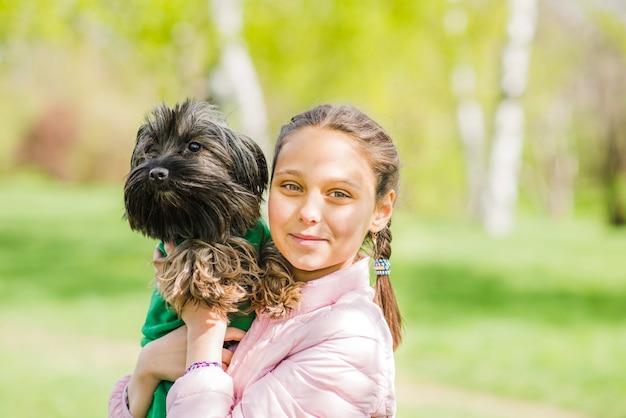 Menina feliz abraçando seu cachorro