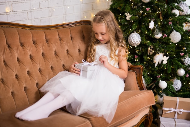 Menina feliz abrindo presente de natal na sala de estar com árvore de natal decorada