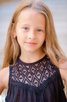 Menina feliz adorável ao ar livre na cidade italiana. retrato de criança caucasiana desfrutar de férias de verão em roma