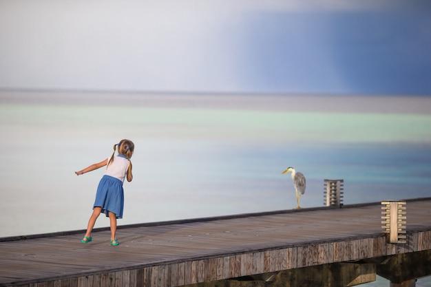 Menina feliz adorável com a garça-real cinzenta em férias da praia