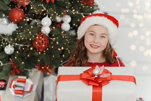 Menina feliz animado segurando a caixa de presente de natal.
