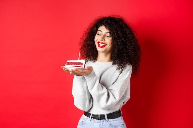 Menina feliz aniversário comemorando e fazendo desejo, segurando o bolo de aniversário e sorrindo, em pé na parede vermelha.