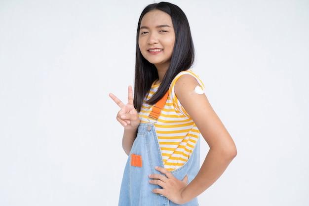 Menina feliz após a vacinação menina asiática no estudante de fundo branco
