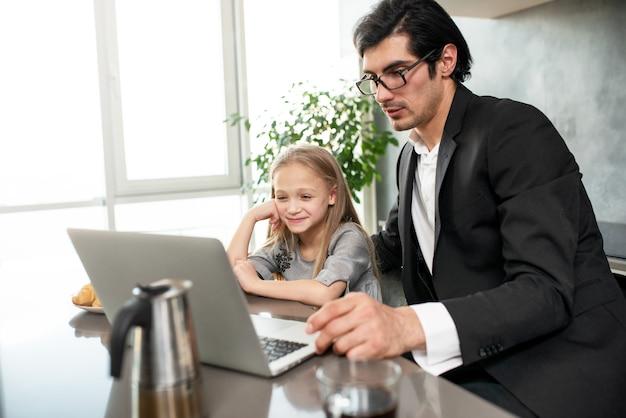 Menina feliz assistindo a um filme no computador com o pai em casa