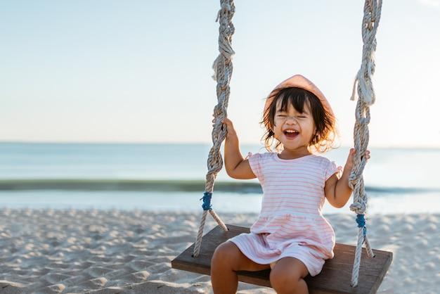 Menina feliz balançando na praia Foto Premium