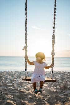 Menina feliz balançando na praia