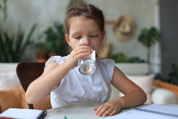 Menina feliz bebe água mineral cristalina em copo, criança pequena recomenda uma dose diária de água limpa