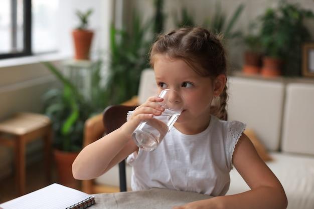 Menina feliz bebe água mineral cristalina em vidro, criança pequena recomenda uma dose diária de água limpa.