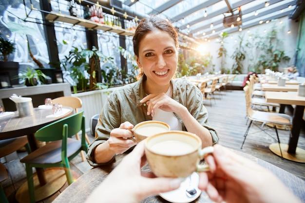 Menina feliz bebendo chá matcha com amigo
