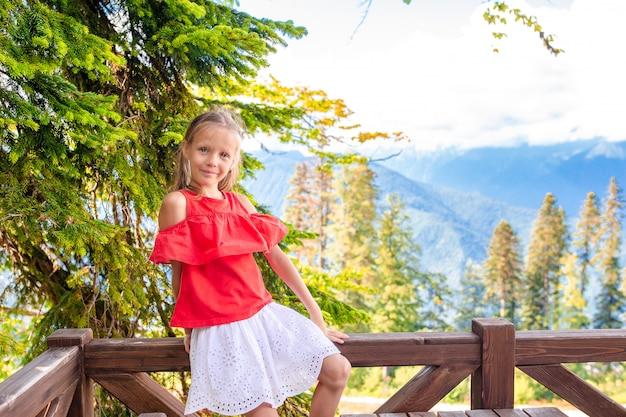 Menina feliz bonita nas montanhas no fundo da névoa