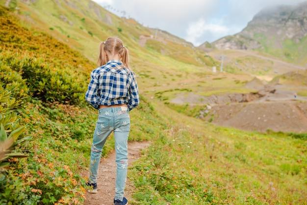 Menina feliz bonita nas montanhas no nevoeiro