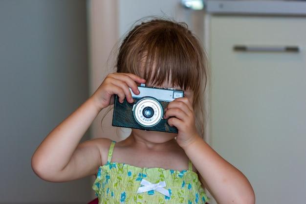 Menina feliz bonitinha com câmera fotográfica vintage
