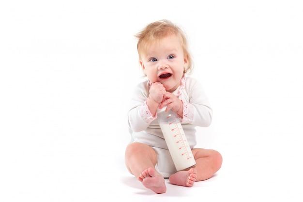 Menina feliz bonitinha na camisa branca com leite