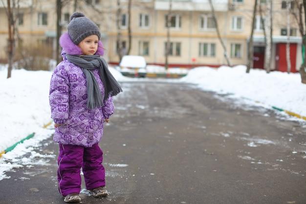 Menina feliz bonito pequeno que anda na neve em um dia de inverno ensolarado ao ar livre