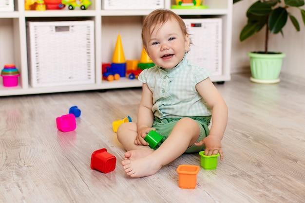 Menina feliz brincando com brinquedos em casa