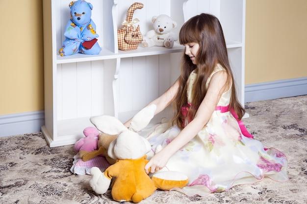 Menina feliz brincando com brinquedos no quarto dela