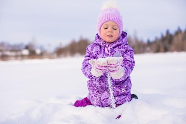 Menina feliz brincando com neve no dia ensolarado de inverno