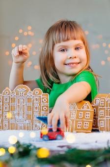 Menina feliz brincando com o brinquedo do carro com a árvore de natal na cidade de biscoitos de gengibre. foco seletivo na garota.