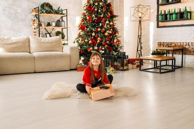 Menina feliz brincando perto da árvore de natal e presentes