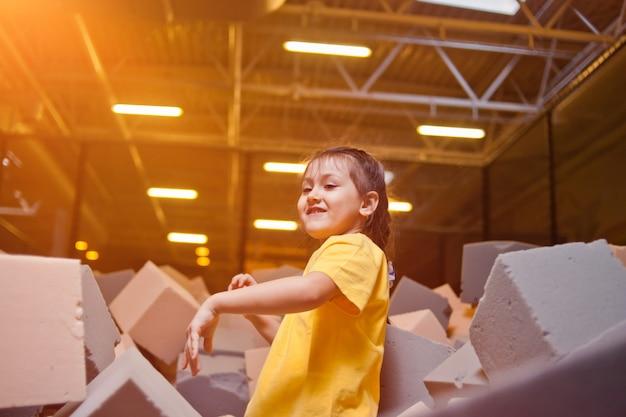 Menina feliz brinque e se divirta em uma piscina seca com cubos paralon em um centro de entretenimento infantil