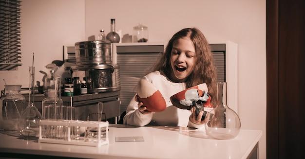 Menina feliz colegial sentada em uma mesa em seu laboratório. o conceito de educação e hobby