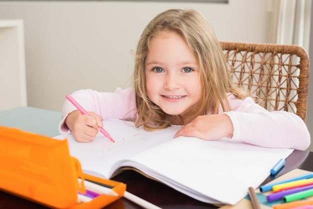 Menina feliz colorir na mesa em casa na cozinha