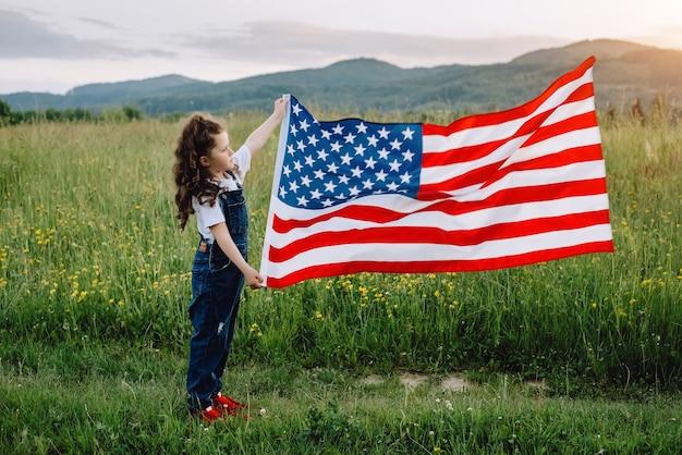 Menina feliz com a bandeira nacional dos eua ao ar livre