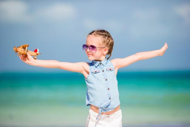 Menina feliz com avião de brinquedo em mãos na praia de areia branca