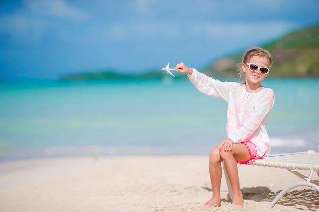 Menina feliz com avião de brinquedo nas mãos na praia de areia branca. brincadeira de criança com brinquedo na praia