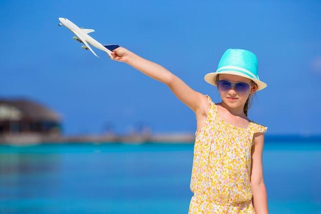 Menina feliz com avião de brinquedo nas mãos na praia de areia branca