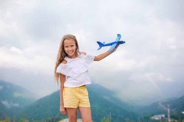 Menina feliz com avião de brinquedo nas mãos nas montanhas