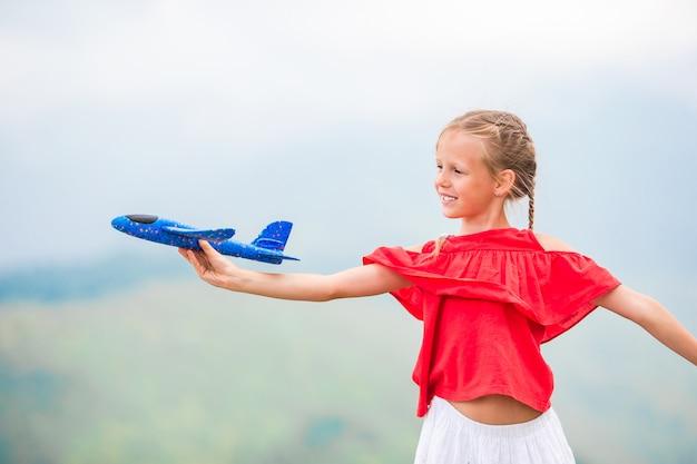 Menina feliz com avião de brinquedo nas mãos