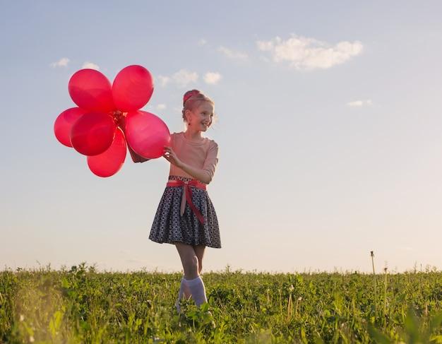 Menina feliz com balões vermelhos ao ar livre