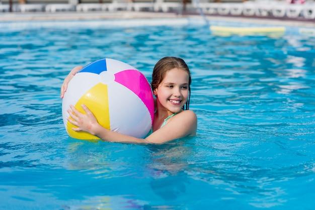 Menina feliz com bola na piscina