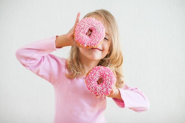 Menina feliz com cabelo loiro brincando e degustando donuts com glacê rosa na festa de hanukkah