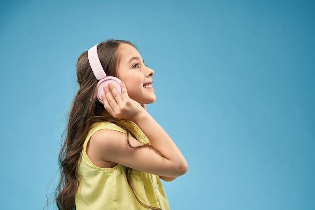 Menina feliz com cabelos longos em fones de ouvido rosa sorrindo.