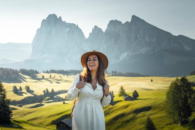 Menina feliz com chapéu branco e mochila em alpe di siusi dolomitas
