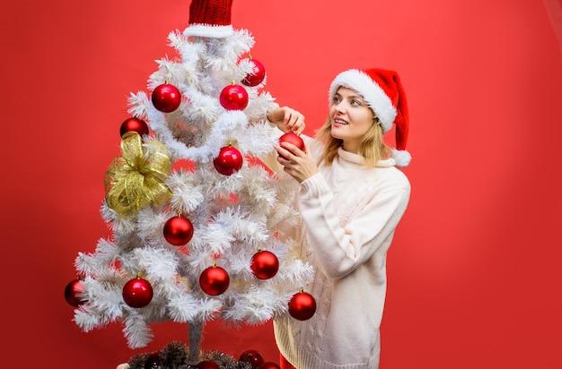 Menina feliz com chapéu de papai noel com árvore de abeto natal ano novo inverno conceito de felicidade mulher sorridente