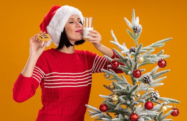Menina feliz com chapéu de papai noel em pé perto da árvore de natal decorada segurando um copo de leite e um biscoito cheirando leite com os olhos fechados, isolado em um fundo laranja