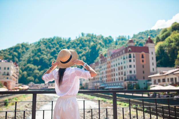 Menina feliz com chapéu no aterro de um rio de montanha em uma cidade europeia.