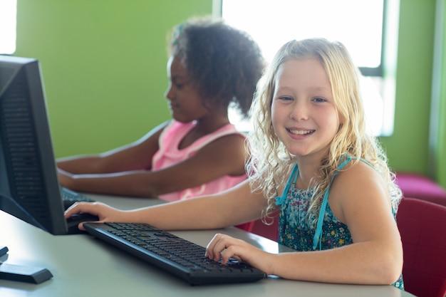 Menina feliz com colega usando computadores