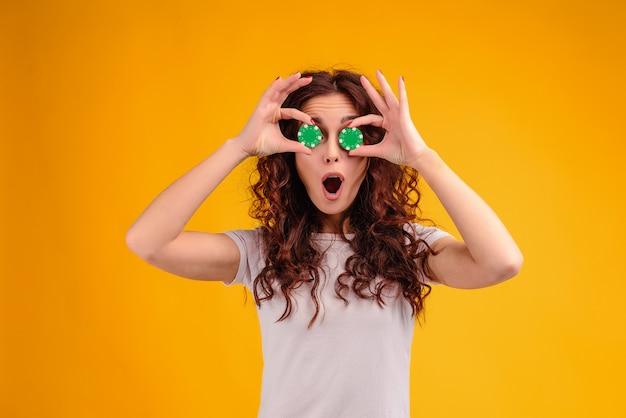 Menina feliz com fichas de poker do casino online na frente de seu rosto isolado sobre o amarelo